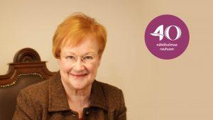 Presidentti Tarja Halonen hymyilee kameralle. Kuvassa on purppura logo, jossa lukee 40 Näkökulmaa rauhaan.